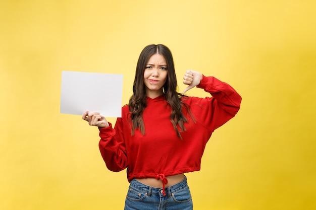 親指を下に示す白紙のシートを保持している若い成人女性