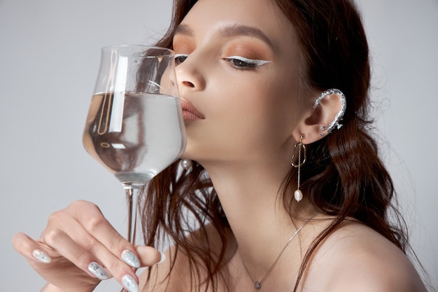 Young adult woman holds a glass of water in her hand near face. beautiful makeup, clean skin