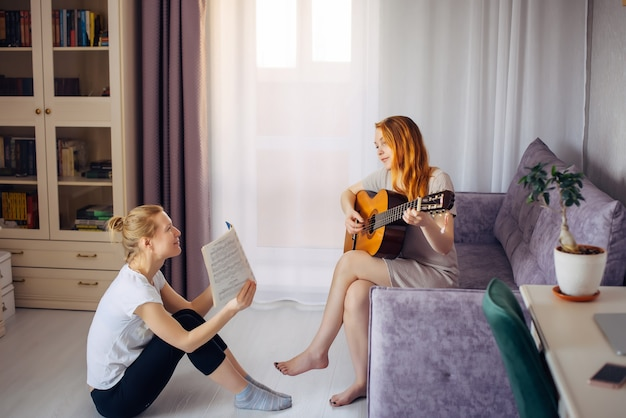 Young adult  woman holds music notebook and looks at her friend playing the guitar. two cute girls play music at home. friendship, love, family leisure, hobbies.