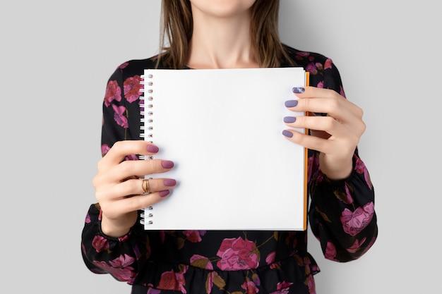 ドレスを着た若い成人女性が空白の開いたメモ帳を保持している