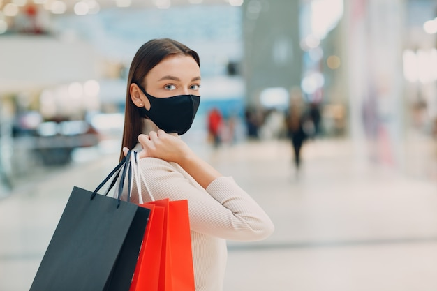 슈퍼마켓에서 손에 종이 쇼핑백을 들고 보호용 의료용 얼굴 마스크를 쓴 젊은 성인 여성