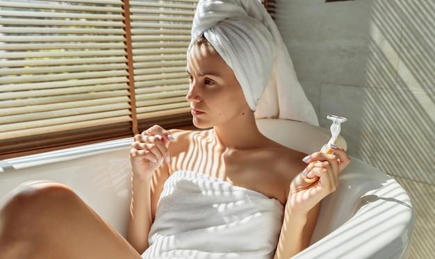 Молодая взрослая женщина лежит в ванной, держа бритву
