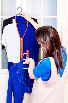 春夏のドレスでワードローブをチェックして片付けを探している若い大人の女性。服を注文するコンセプト