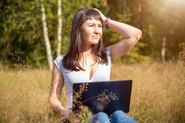Молодая взрослая женщина в панике смотрит на ноутбук и держит голову. проблемы с сетью. содержание шока