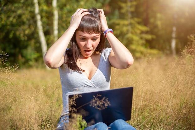 Молодая взрослая женщина в панике смотрит на ноутбук и держит в голове проблемы с сетью