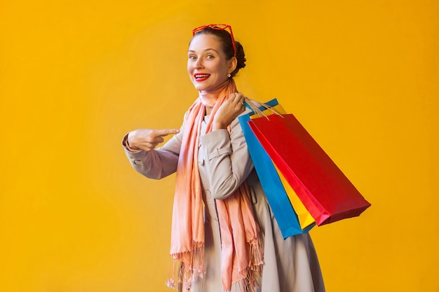 Young adult woman pointing finger on bags and looking at camera and toothy smile. on yellow background. studio shot