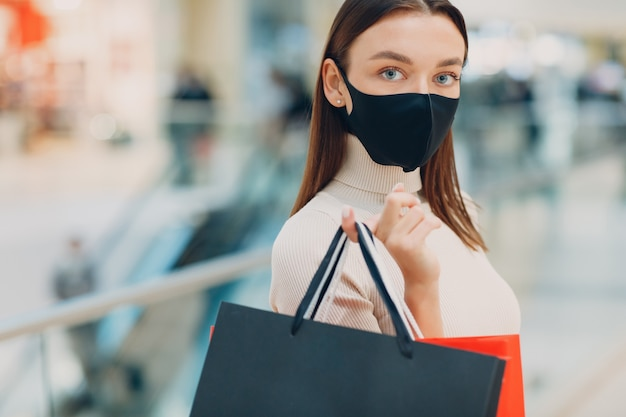 Young adult woman in protective medical face mask carrying paper shopping bags in hands at retail store mall