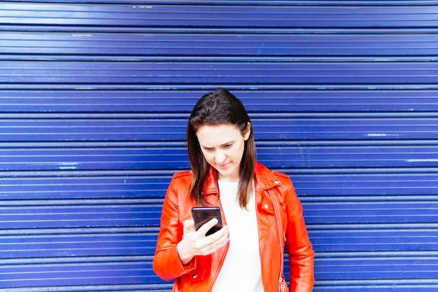 파란색 배경으로 스마트폰을 읽는 젊은 성인 여성