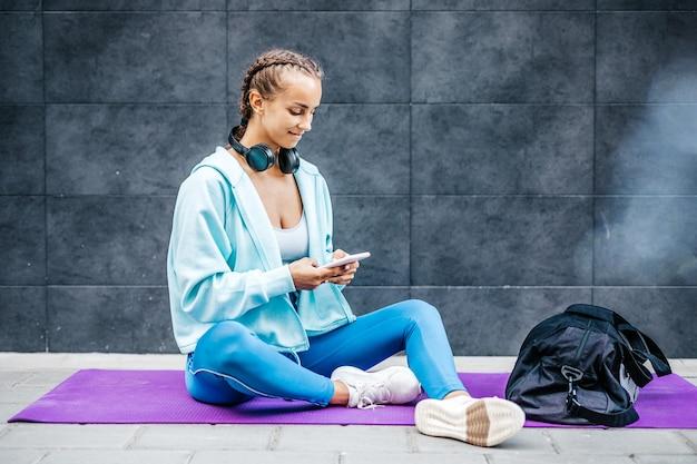 피트니스 훈련 후 휴식을 취하는 젊은 성인 여성. 그녀는 앉아서 누군가와 의사 소통하기 위해 스마트 폰을 사용하고 있습니다.