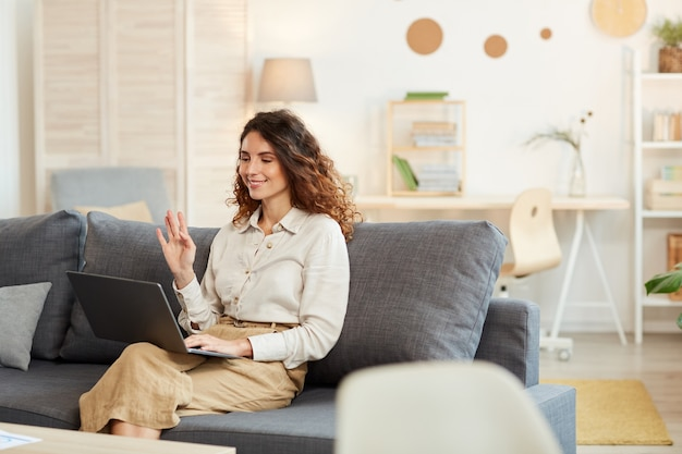 Young adult woman sitting in sofa at home participating in video conference, greeting her colleagues