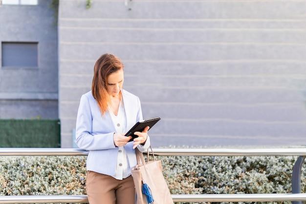 ビジネスタブレットをチェックして美しい実業家を笑顔の若い大人の女性。成功したビジネスウーマンのコンセプト。コピースペース