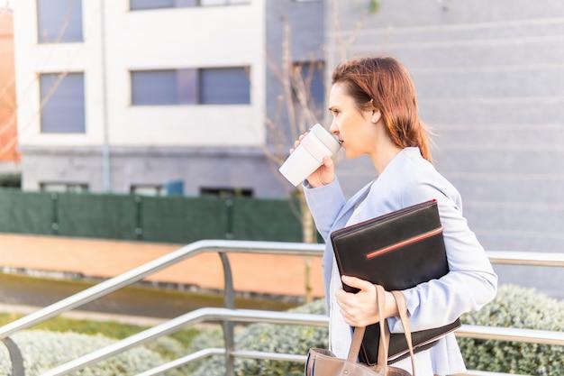 ラップトップとフォルダーに行くためにコーヒーと一緒に仕事を残して美しい実業家を笑顔の若い大人の女性。成功したビジネスウーマンconcept.copyスペース