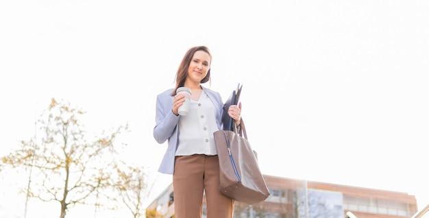 Молодая взрослая женщина улыбается красивая бизнесвумен, оставляя работать с кофе, чтобы пойти ноутбук и папку. концепция успешной деловой женщины. копией пространства