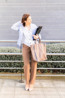 Молодая взрослая женщина улыбается красивая бизнесвумен, ждет на улице клиента с ноутбуком и папкой. концепция успешной бизнес-леди. копировать пространство