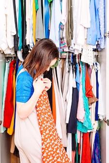 봄과 여름의 도착을 위해 옷장에서 옷을 분류하는 젊은 성인 여성