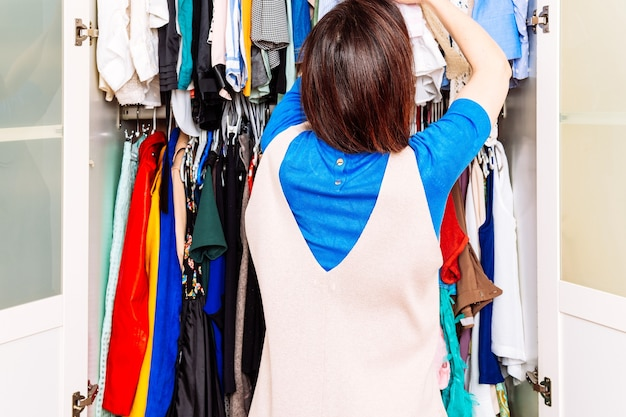 가정 탈의실에서 봄 여름 드레스를 분류하는 젊은 성인 여성