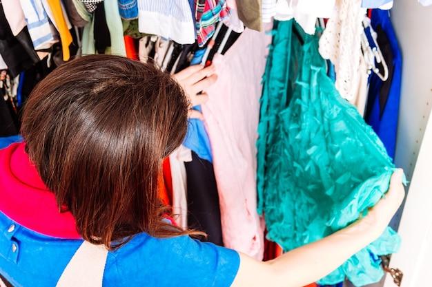 Молодая взрослая женщина перебирает весенние летние платья в домашней гримерке