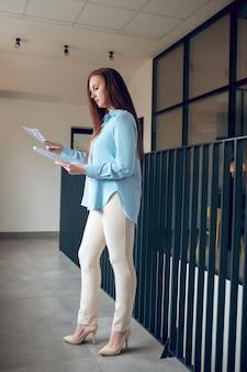 Молодая взрослая женщина, стоящая, глядя на документы.
