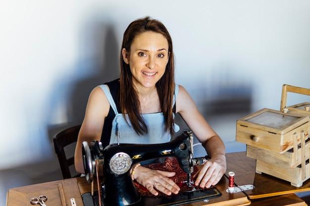 Молодая взрослая женщина портной работает на своей старой швейной машине