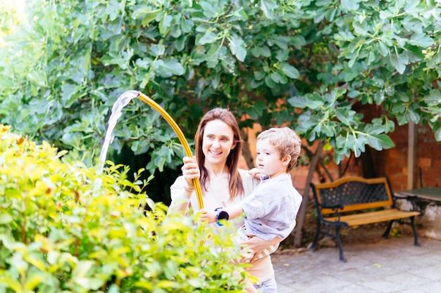 彼女の3歳の息子と一緒に庭に水をまく若い大人の女性