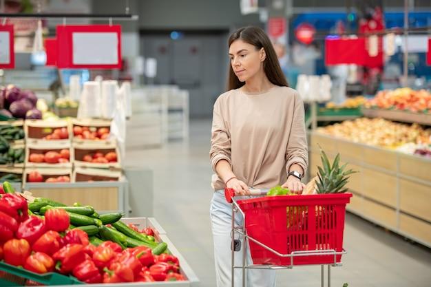 現代の店で購入するものを選択するショッピングカートと通路に沿って歩くカジュアルな服を着ている若い大人の女性