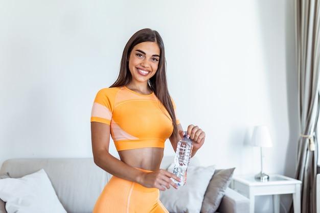 집에서 훈련 후 쉬고 플라스틱 병에서 아름 다운 몸 식 수와 젊은 성인 여자.