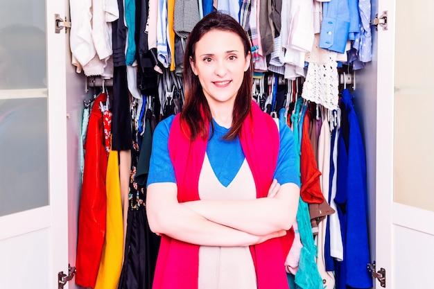 Молодая взрослая женщина со скрещенными руками перед ее гардеробной, полной платьев. шопоголическая концепция.