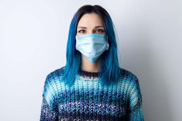 파란 머리를 가진 젊은 성인 여자 보호 마스크를 착용.