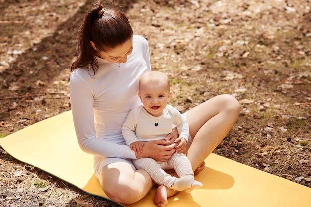 Giovane donna adulta con i capelli scuri che indossa abiti bianchi seduta sul karemat e tiene in braccio un neonato