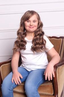 얼굴에 행복 한 미소로 고립 된 벽에 다운 증후군을 가진 젊은 성인 여자.