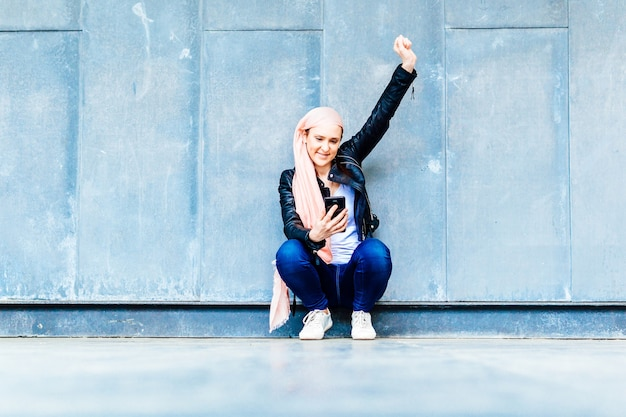 Young adult woman with pink head scarf against cancer squatting with raised arm in sign of victory