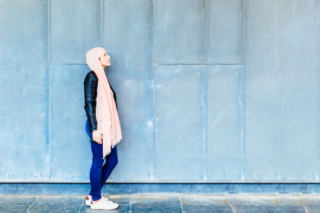 Young adult woman with pink headscarf against cancer in profile looking up with copyspace