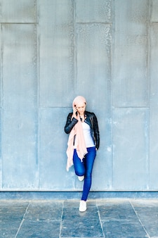 Young adult woman with pink headscarf against cancer talking on the phone over gray neutral blackboard background. middle-aged cancer concept