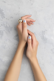 Young adult womans hand with fashionable nails on white background. spring summer nail design. manicure, pedicure beauty salon concept.