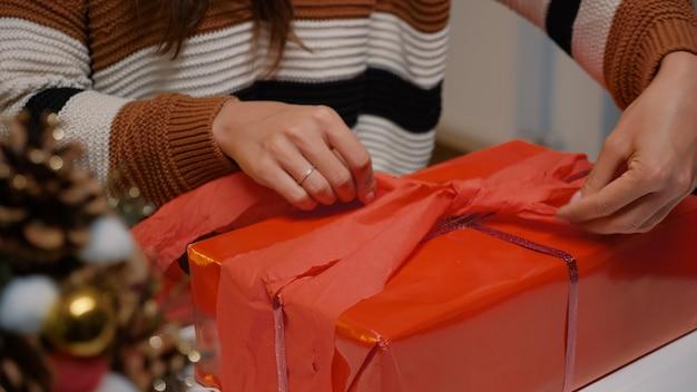 Молодой взрослый упаковывает подарочную коробку в красную бумагу