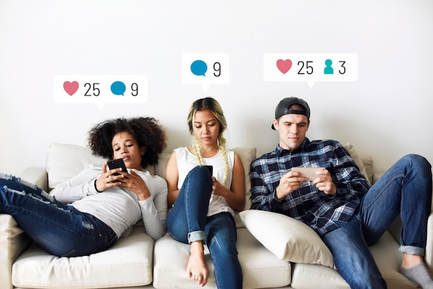 Young adults on the couch using social media on their smartphones