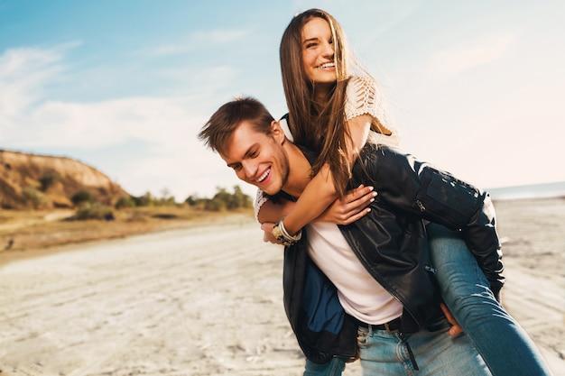 若い大人のガールフレンドとボーイフレンドは幸せを抱き締めます。ビーチ沿いの日当たりの良い春に恋に若いきれいなカップル。暖かい色。