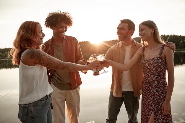 젊은 성인 다인종 친구 커플은 즐거운 시간을 보내고, 함께 레드 와인, 맥주, 사이다를 함께 축하하며 일몰 배경 부두에서 함께 술을 마시고 웃고, 환호합니다. 폐쇄 후