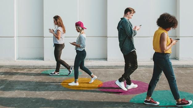 Молодые люди с помощью смартфонов гуляют на свежем воздухе