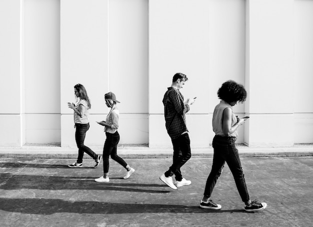 Giovani adulti che usano gli smartphone mentre camminano all'aperto