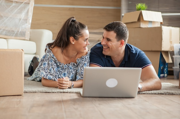 新しい家具のために新しいアパートでラップトップを使用している若い大人