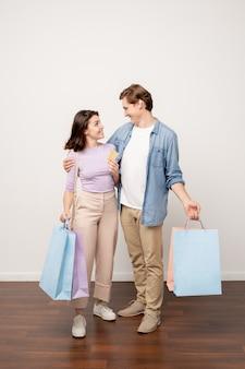 黒い金曜日に買い物に成功した後お互いを見てカジュアルウェアの愛情のこもったカップル