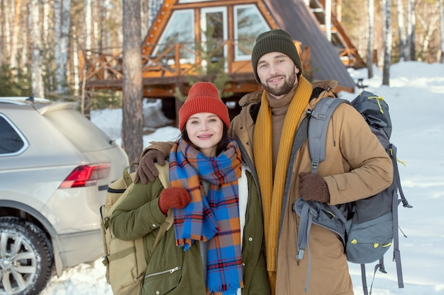 彼らの車とカントリーハウスに対してカメラの前に立って、外であなたを見ている暖かい冬服の若い愛情のこもったカップル