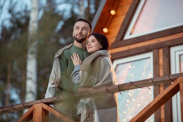 森の木々を背景にカントリーハウスに立ち、日の出を見ながら格子縞に包まれた若い愛情のこもったカップル