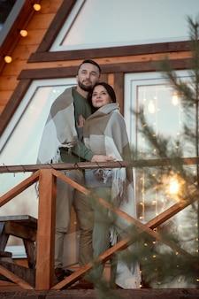 新しい大きなカントリーハウスのそばに立って、朝の日の出を見ている格子縞に包まれた若い愛情のこもったカップル