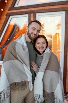 彼らの新しいカントリーハウスの窓に対してカメラの前に立ってあなたを見ている格子縞に包まれた若い愛情のこもったカップル