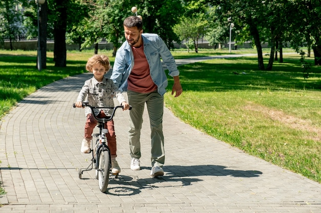 Young affectionate father in casualwear helping his cute little son riding on bicycle along road in public park on sunny summer weekend