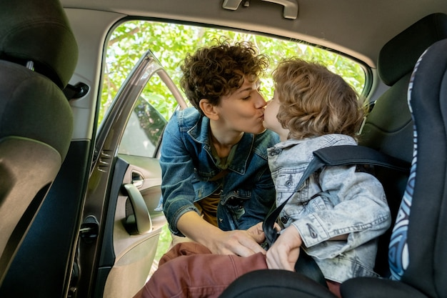 Young affectionate pretty woman in denim jacket kissing her cute little son on mouth while both going to go somewhere by car on summer day