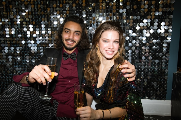 Young affectionate sweethearts with flutes of champagne cheering up at party in night club in front of camera