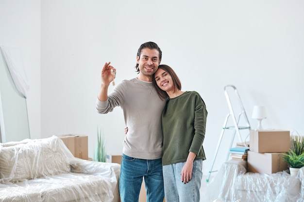 Молодая ласковая женщина обнимает мужа с ключом от их нового дома или квартиры, в то время как обе стоят в комнате с распакованными вещами
